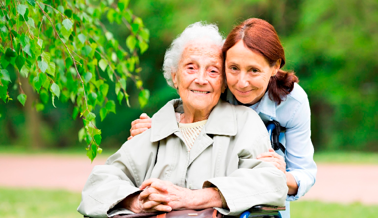 Woman hugging her elderly mother with a green natural background