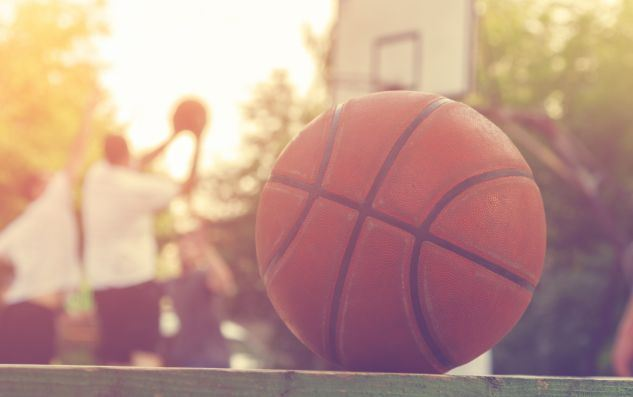 Basketball-ball-on-a-bench-with-defocused-players-in-the-background