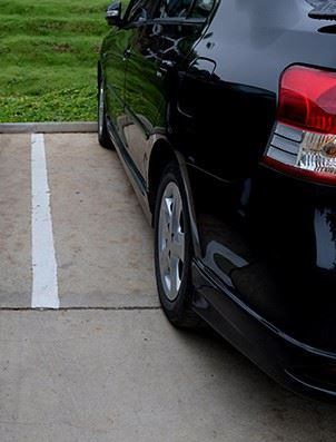 Car parking in a parking lot with a white line separating