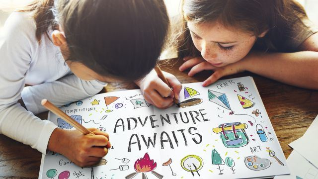 Two girls coloring and drawing on an Adventure Awaits poster over a wooden table