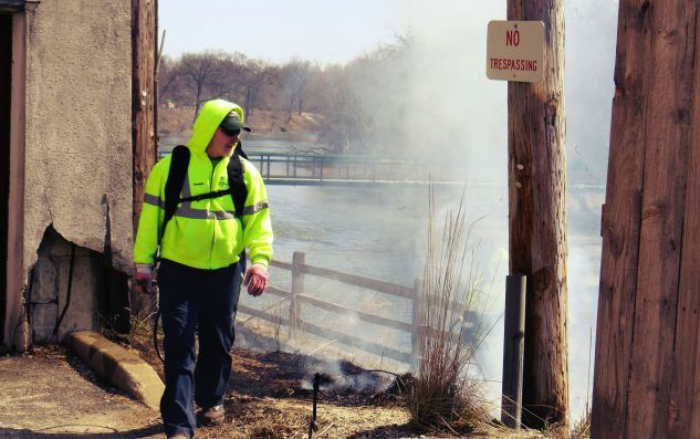 Village Forester walking next to the controlled burn near the river