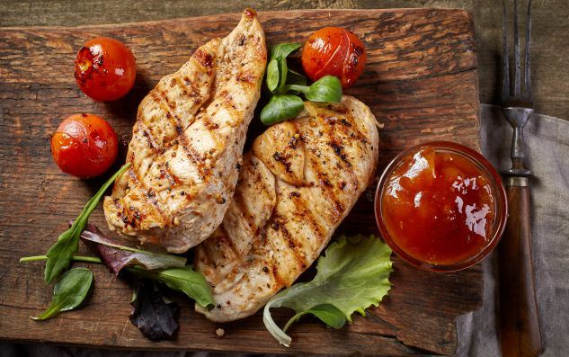 grilled-chicken-fillets-on-wooden-cutting-board