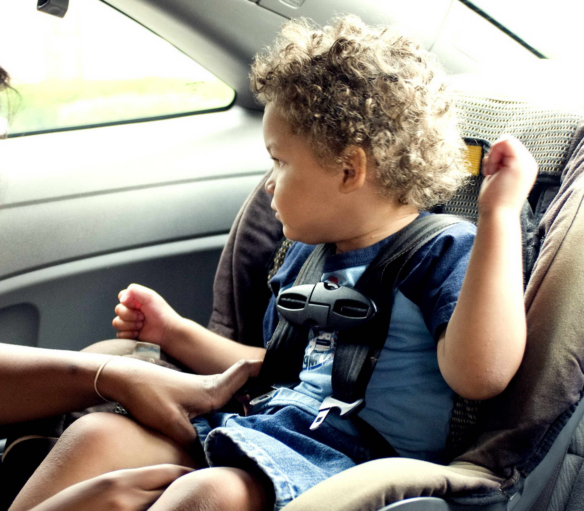 Mother Adjusting Seat Belt on Child