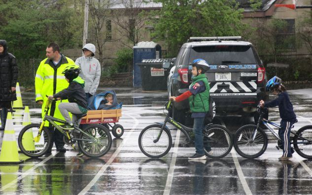 Children on Bikes on a rainy day with police helping